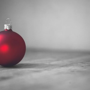 christmas is coming, red christmas tree ornament on color-desaturated grey background